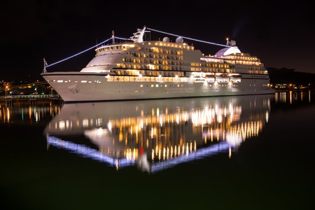 Large luxury cruise ship on sea water at night with illuminated light docked at port of st.Johns, Antigua
