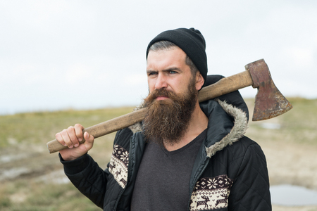 Handsome man hipster or guy with beard and moustache on serious face in hat and jacket holds rusty axe with wooden hilt outdoor on mountain top against cloudy sky on natural background, copy space