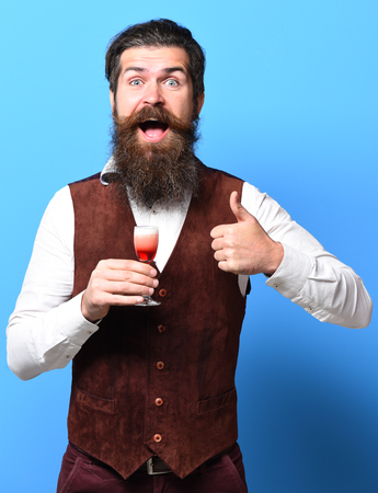 handsome bearded man with long beard and mustache on smiling face tasting glass of alcoholic shot in vintage suede leather waistcoat on blue studio background Stock Photo