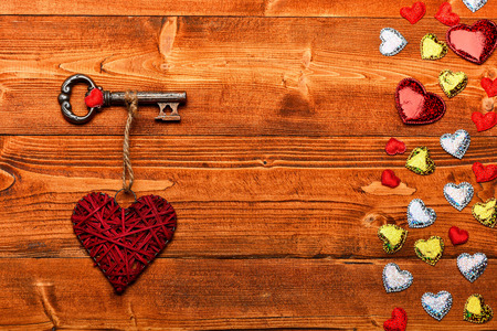 Set of colorful little valentine hearts and metallic key with big handmade heart on brown vintage wooden background, top view