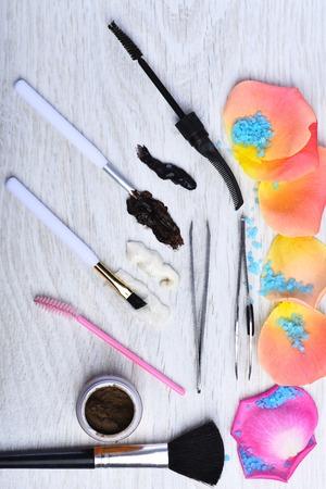 tinte cabello: conjunto de tinte para el cabello, esponja de maquillaje, cepillos, cepillo de cejas, sombra de ojos, pinzas con pentals de rosa y sal azul sobre fondo blanco de madera de color gris, vista desde arriba Foto de archivo