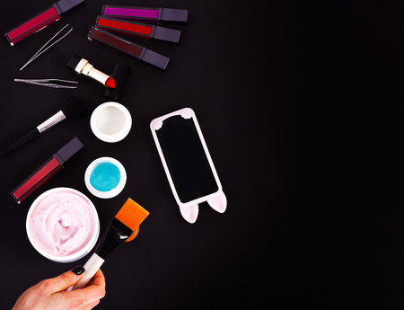 powder puff: set of various cosmetics: cream, gel, lipsticks, lip gloss, brushes, powder puff, tweezers, cell phone and brush in hands isolated on black background, copy space, top view