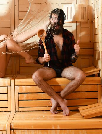 bather: Excited man or bearded hipster in red checkered shirt and sexy female legs wet with big splash of water. Male bather gives thumbs up gesture with spoon in sauna, thermal bath on wooden background