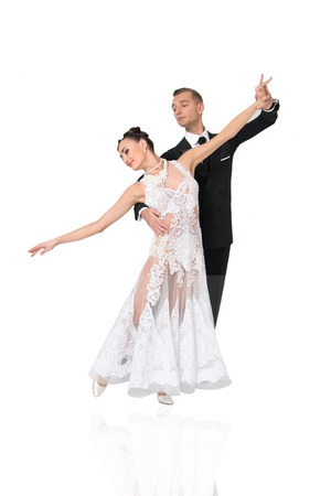 beautiful ballroom dance couple in a dance pose isolated on white background. sensual professional dancers dancing walz, tango, slowfox and quickstep