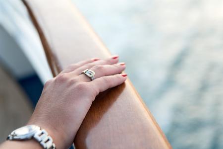 Mani femminili e orologio da polso con il manicure rosso e anello d'oro al dito con diamanti in prossimità di acqua Archivio Fotografico - 71870827