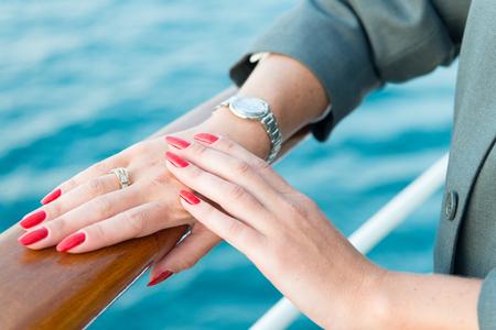 Mani femminili e orologio da polso con il manicure rosso e anello d'oro al dito con diamanti in prossimità di acqua Archivio Fotografico - 71870837