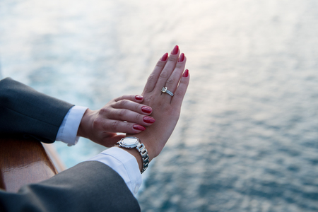 Female hands and wrist-watch with red manicure and golden ring on finger with diamonds near water Stock Photo