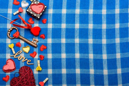 white and blue plaid fabric or checkered cloth background with small decoration red heart of straw, love symbol silver and gold colors little sweet box, clothespins and metallic key, copy space
