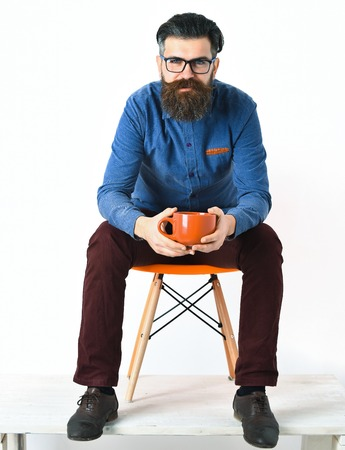 unshaven: Bearded man, long beard. Brutal caucasian unshaven serious hipster with glasses and moustache holding orange mug, sitting on chair, wearing black fashion shoes isolated on white background Stock Photo