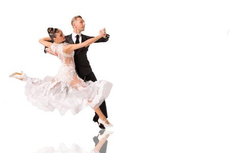mooie ballroom dans paar in een dans pose op een witte achtergrond. sensuele proffessionele dansers dansen wals, tango, quickstep en Slowfox