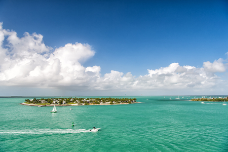 cruise touristic boats or yachts floating by island with houses and green trees on turquoise water and blue cloudy sky, yachting and isle life around beautiful Key West Florida, USA