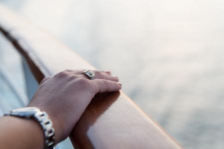 Mani femminili e orologio da polso con il manicure rosso e anello d'oro al dito con diamanti in prossimità di acqua Archivio Fotografico - 74050676