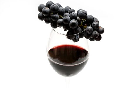 Glass of tasty dark red wine and bunch of black grapes isolated on white background
