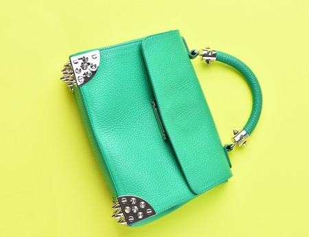clutch bag: Nice beautiful small womans leather green fashionable bag with decorative metallic spikes or thorns on yellow background Stock Photo