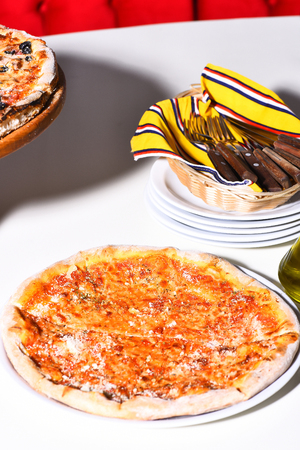 Tasty pizza served on white plate served with utensils in pizzeria, cafe or restaurant on white table background