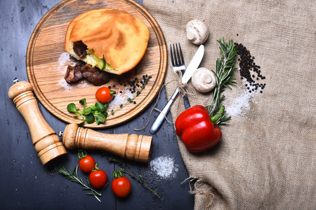 pepperbox: calzone or pie with meat, fresh red cherry tomato, sweet pepper, mushroom, rosemary, thyme, corn salad, salt on wooden tray, pepperbox, saltcellar, silver fork, knife on grey background with burlap