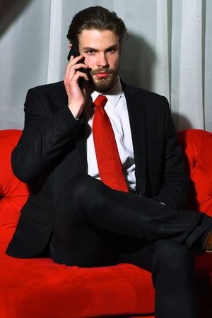 red sofa: caucasian hipster with moustache speaking on mobile or cell phone has serious face, unshaven guy with stylish hair in suit and red tie sitting on sofa Stock Photo
