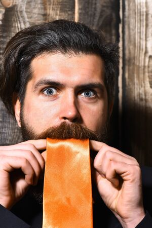 caucasian shouting hipster with moustache in suit holding acid orange tie on brown vintage wooden studio background Reklamní fotografie