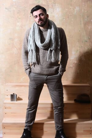 metallic stairs: caucasian hipster with moustache in sweater and scarf posing next to stairs with hat and flask with serious face on studio wall background