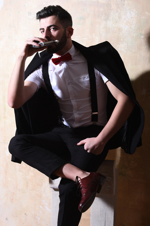 bearded man, long beard, brutal caucasian hipster with moustache in black elegant suit with bow-tie is sitting on chair, holding and drinking from flask with serious face on studio wall background