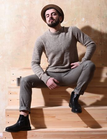 metallic stairs: bearded man, long beard, brutal caucasian hipster with moustache in sweater sitting on wooden stairs with hat and flask with serious face on studio wall background Stock Photo