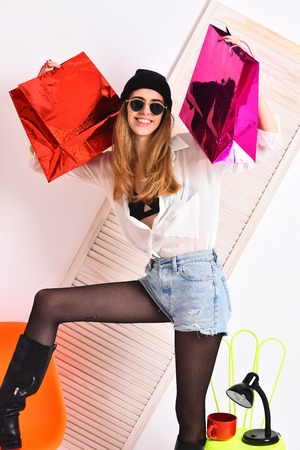 pretty woman or sexy cute girl with long blonde hair and happy face in sunglasses, boots, hat, at orange and light green chair with lamp, red tea cup, shopping bag, package on white background