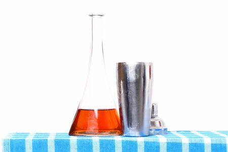 glass flask or bottle with alcohol and metallic opened shaker on blue checkered plaid isolated on white background Stock Photo