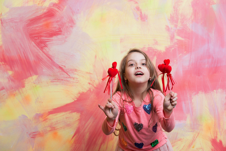 small baby girl or cute child with happy face and blonde hair in in pink shirt holding red valentines day holiday decorative hearts on colorful abstract background, copy space