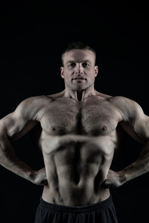 sexi: handsome bodybuilder man or sexy muscular guy with athlete body, torso and chest training sport and posing in gym on black background