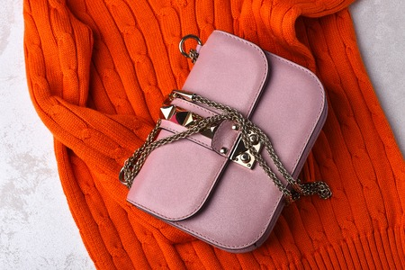 Nice beautiful small womans leather pink fashionable bag with decorative metallic spikes, thorns and chain on white background with orange sweater