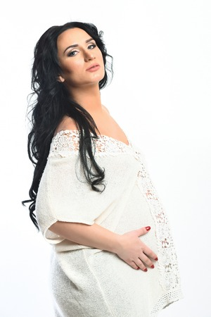 Pretty cute pregnant woman stroking her belly with hands in beige knitted tunic with openwork rim and curly long hair isolated on white studio background