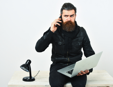 Bearded man, long beard. Brutal caucasian unshaven hipster sitting on table with lamp on, holding laptop and speaks by cell phone in black leather jacket isolated on white studio background