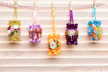 easter colorful eggs decorated with bright color ribbon and beads hanging on clothespin on wooden background, spring holiday celebration