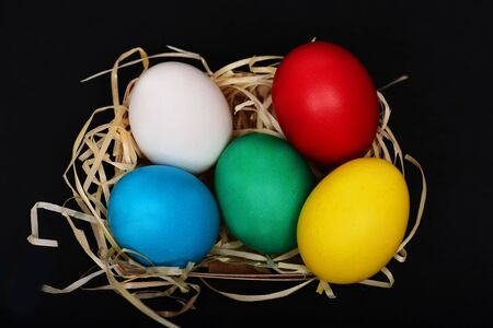 easter colorful eggs painted in bright colors in wooden basket with straw nest isolated on black background, spring holiday celebration Stock Photo