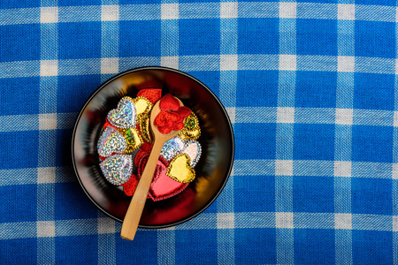 valentine decoration, set of ceramic plate with wooden spoon and beautiful colorful hearts symbol of love on white and blue plaid fabric or checkered cloth background, copy space