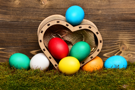 easter colorful eggs painted in bright colors in wooden box in shape of heart on wood background with green moss, spring holiday celebration, copy space Stock Photo