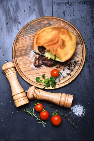 pepperbox: calzone or pie with meat, fresh red cherry tomato, mushroom, rosemary, thyme, corn salad, pepper, salt on wooden tray, pepperbox, saltcellar on grey background