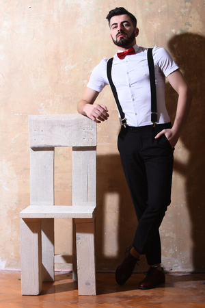 reggicalze: bearded man, long beard, brutal caucasian hipster with moustache in white shirt and suspenders with bow-tie posing next to wooden chair with serious face on studio wall background