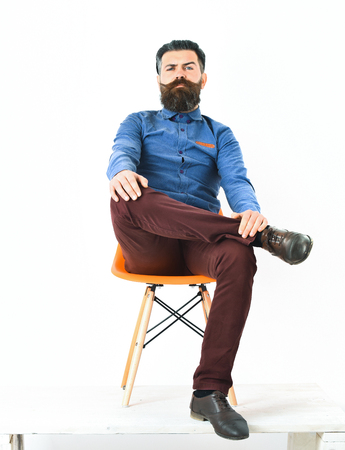 Bearded man, long beard. Brutal caucasian serious hipster with moustache sitting on orange chair wearing blue shirt, vinous pants and black shoes isolated on white background