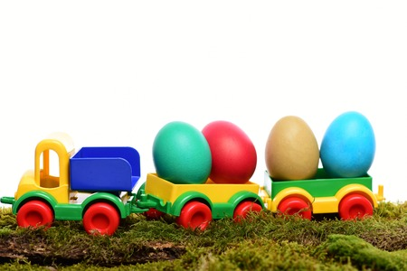 easter colorful eggs painted in bright colors in plastic car toy isolated on white background with moss, spring holiday celebration, copy space Stock Photo