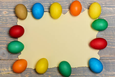 papel quemado: set of colorful eggs on burnt paper on grey vintage wooden background. Happy Easter concept, copy space