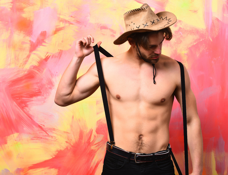 suspender: Bearded man, short beard. Caucasian sexy macho man with moustache shows six packs and abs on muscle torso on athletic body in pants with suspenders and cowboy hat on colorful studio background Stock Photo