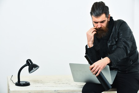 Bearded man, long beard. Brutal caucasian unshaven hipster sitting on table with lamp and bottle on, holding laptop in black leather jacket isolated on white studio background, copy space Stock Photo