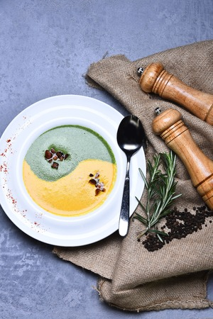 pepperbox: spinach and pumpkin cream soup or puree green and yellow color in infinity sign with silver spoon on white plate near wooden pepperbox, saltcellar, rosemary, pepper and burlap on grey background Stock Photo