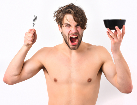 Bearded man, short beard. Caucasian sexy young macho with stylish hair, moustache on shouting face shows muscular torso holding black bowl with fork isolated on white studio background