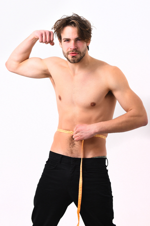 Bearded man, short beard. Caucasian sexy young macho with stylish hair, moustache, uses measuring tape on muscular torso isolated on white studio background