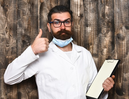 postgraduate: Bearded man, long beard. Brutal caucasian doctor or unshaven hipster, postgraduate student holding clipboard in medical gown and mask on brown wooden vintage studio background. Medicine concept