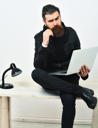 Bearded man, long beard. Brutal caucasian unshaven hipster sitting on table with lamp on, holding laptop in black leather jacket isolated on white studio background