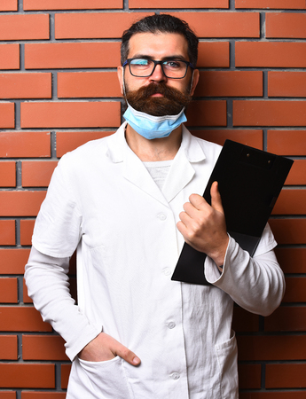postgraduate: Bearded man, long beard. Brutal caucasian doctor or unshaven hipster, postgraduate student holding clipboard in medical gown and mask on brown brick wall studio background. Medicine concept