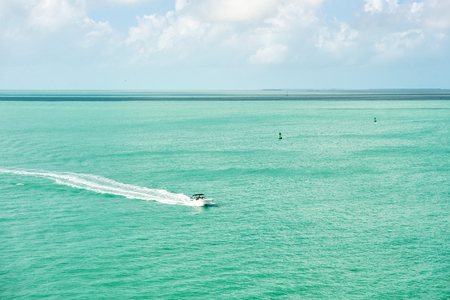 cruise touristic boat or yacht floating on turquoise water and blue cloudy sky, yachting and sport, traveling and vacation, Key West Florida, USA